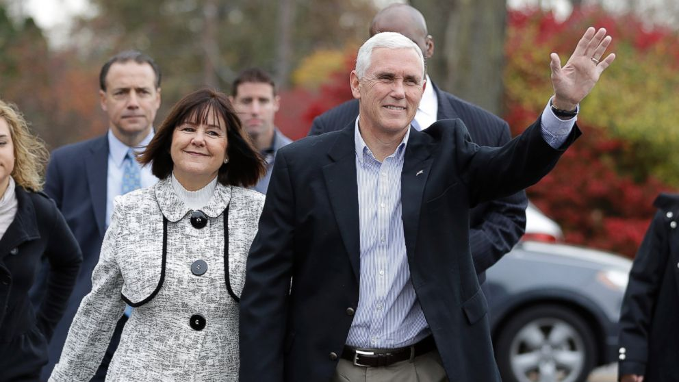 Republican vice presidential candidate, Indiana Gov. Mike Pence, accompanied by his wife, Karen, waves as they go to cast their ballots, Nov. 8, 2016, in Indianapolis.