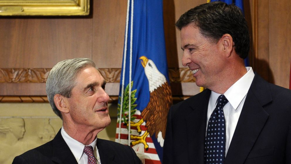A Sept. 4, 2013 file photo showing incoming FBI Director James Comey, right, talking with retiring FBI Director Robert Mueller at the Justice Department in Washington,D.C.