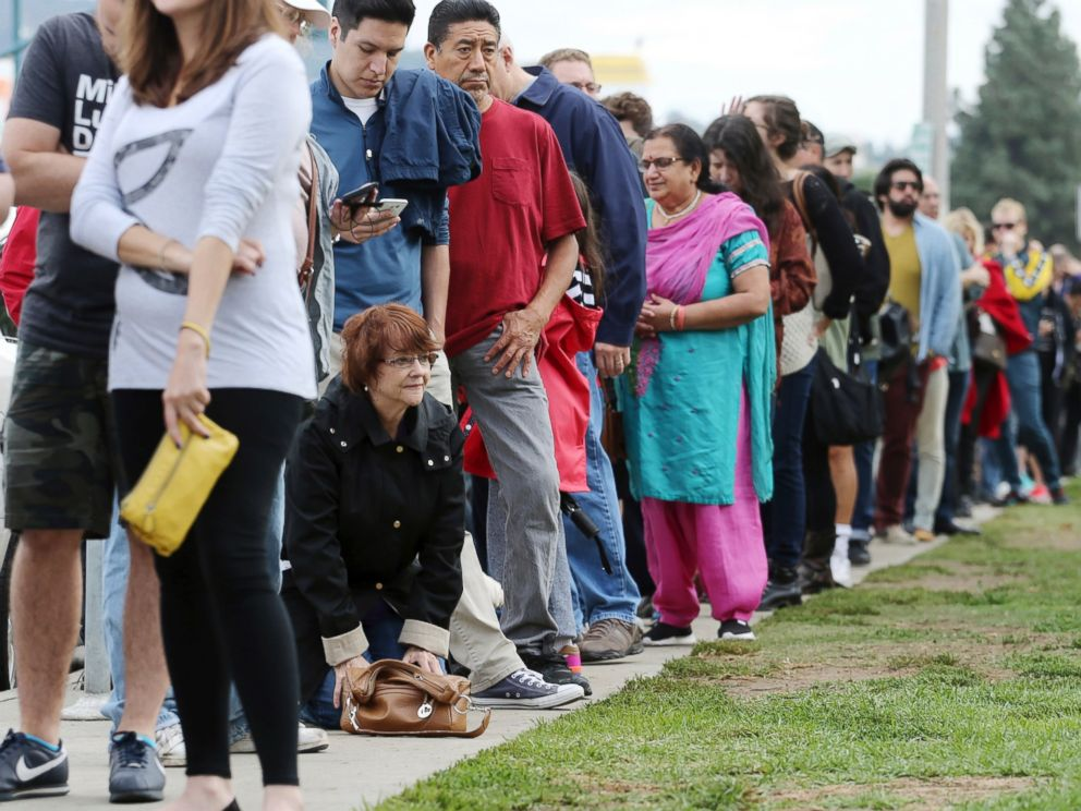 PHOTO: A woman kneels to take a back break while waiting in line at a weekend early voting polling place at the North Hollywood branch library in Los Angeles, Calif., Oct. 30,2016.