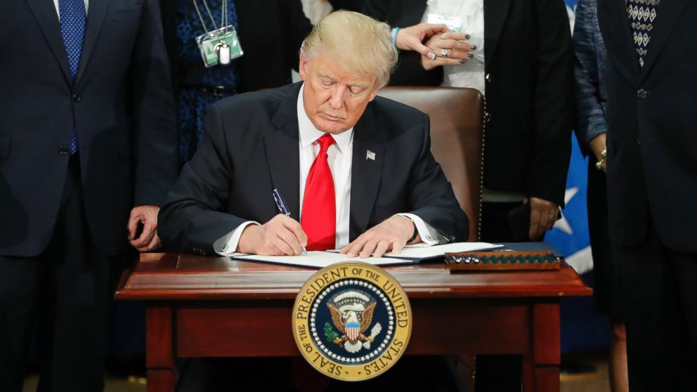 President Donald Trump signs an executive order for border security and immigration enforcement improvements at the Department of Homeland Security in Washington, Jan. 25, 2017.