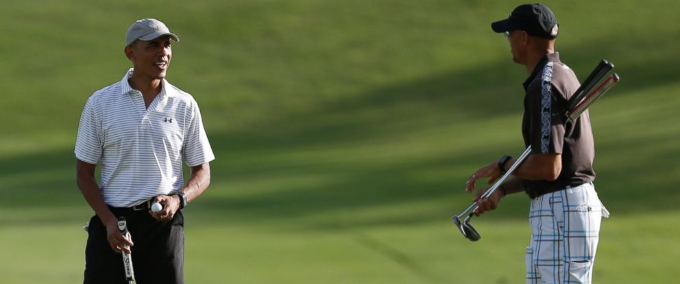 PHOTO: President Barack Obama looks to Darrell Harrington as they golf the 18th green at Kapolei Golf Club, in Kapolei, Hawaii.