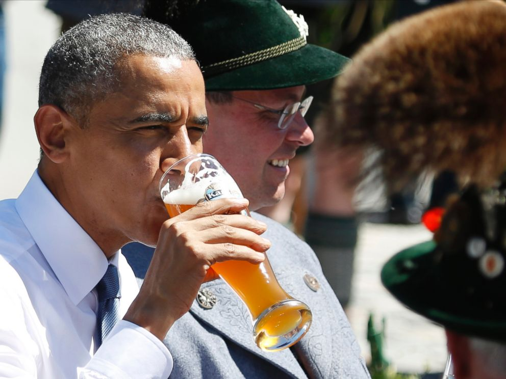 U.S. President Barack Obama drinks a beer as he sits between men dressed in traditional Bavarian clothes during a visit to the village of Kruen, southern Germany, Sunday, June 7, 2015 prior to the G-7 summit.