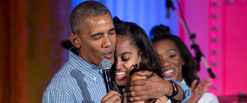 """PHOTO: President Barack Obama hugs and sings """"Happy Birthday"""" to his daughter Malia Obama on stage during an Independence Day celebration in the East Room of the White House, in Washington, July 4, 2016, for members of the military and their families."""