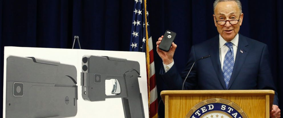 Standing beside photographs of a new product, Sen Charles Schumer shown holding an iPhone 5S, voices his opposition to a handgun that appears to be a cell phone during a news conference in his office, April 4, 2016, in New York.