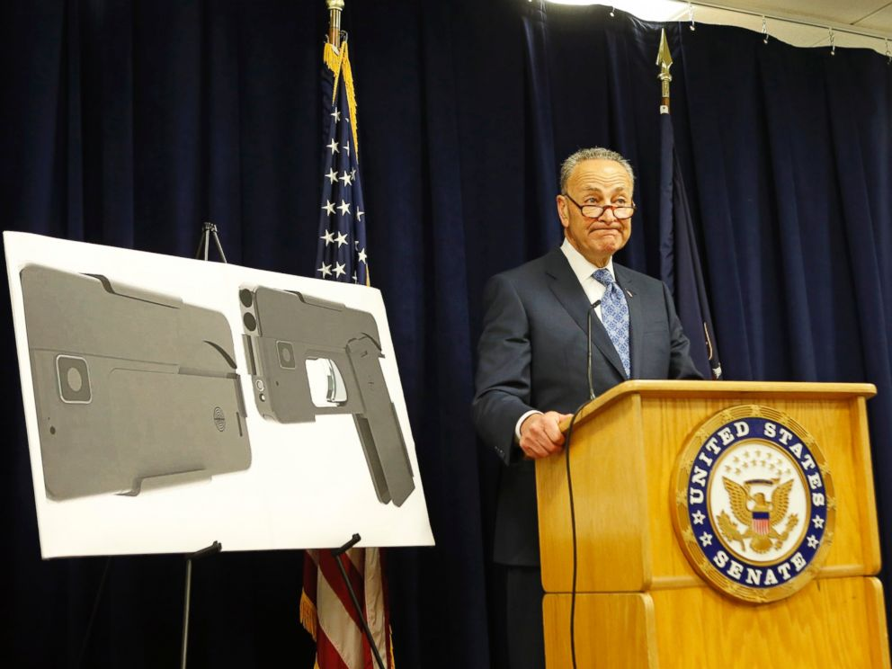 U.S. Sen Charles Schumer stands beside two photographs of what appears to be a cell phone, but is actually a handgun, during a press conference in his office, April 4, 2016, in New York.