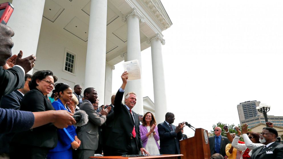 Terry McAuliffe holds up the order he signed to restore rights to felons in Virginia at the Capitol in Richmond, Virginia, April 22, 2016.
