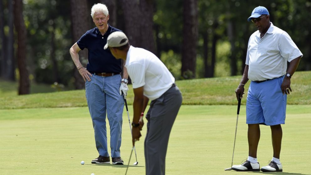 President Barack Obama, center, watches his putt as he plays golf with former President Bill Clinton, left, and Amb. Ron Kirk, right, former United States Trade Representative, on the first hole at Farm Neck Golf Club in Oak Bluffs, Mass., on Martha's Vineyard, Aug. 15, 2015.