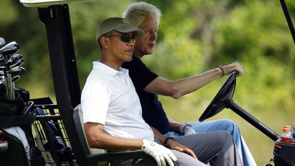 President Barack Obama, front left, and former President Bill Clinton ride in a cart while golfing at Farm Neck Golf Club in Oak Bluffs, Mass. on the island of Martha's Vineyard, Aug. 15, 2015.