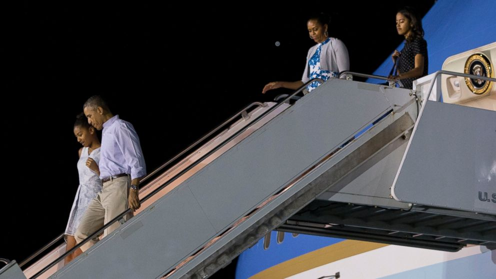 President Barack Obama walks with Sasha Obama as first lady Michelle Obama walks with Malia Obama, as the first family arrives at Pearl Harbor, Hawaii to begin their family vacation, Dec. 19, 2014.