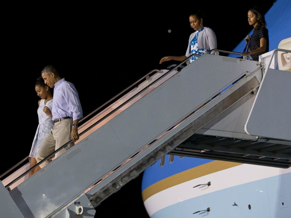PHOTO: President Barack Obama walks with Sasha Obama as first lady Michelle Obama walks with Malia Obama, as the first family arrives at Pearl Harbor, Hawaii to begin their family vacation, Dec. 19, 2014.