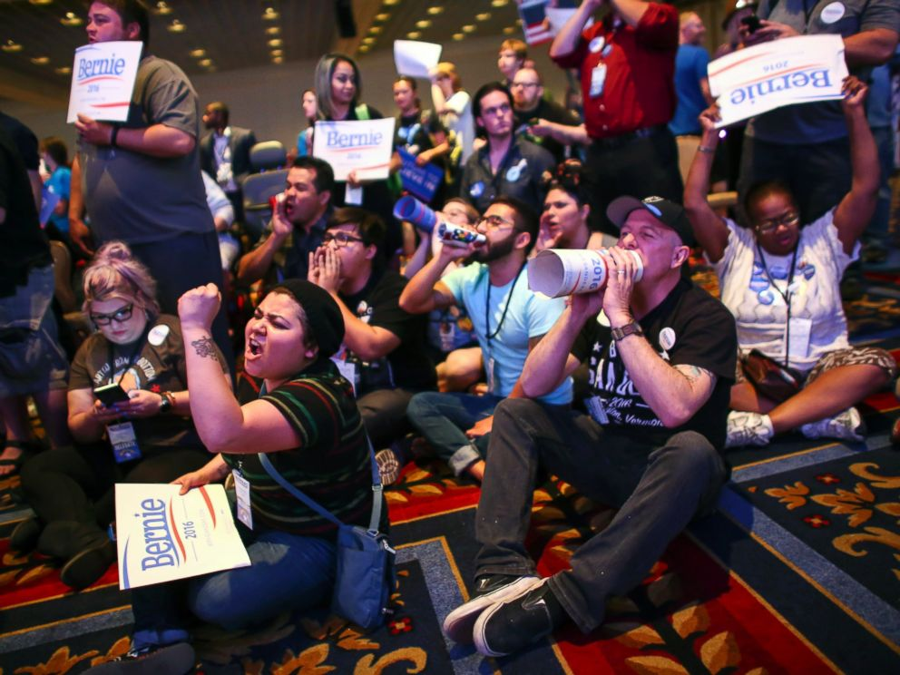 PHOTO: Supporters of Democratic presidential candidate Bernie Sanders, including Valeria Romano, center left, and Johnny Hancen, center right, gather in the front of the room during the Nevada State Democratic Party, May 14, 2016.