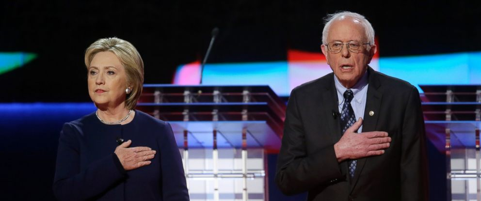 PHOTO: Democratic presidential candidates Hillary Clinton, left, and Sen. Bernie Sanders, stand on stage during the National Anthem before a Democratic presidential primary debate at the University of Michigan-Flint, March 6, 2016, in Flint, Mich.