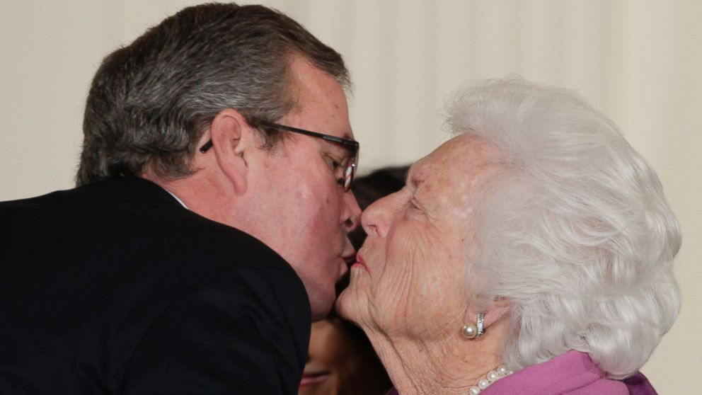 Former first lady Barbara Bush, right, greets her son former Fla. Gov. Jeb Bush, with a kiss as she arrives at the 2010 Presidential Medal of Freedom ceremony, in this Feb. 15, 2011, file photo.