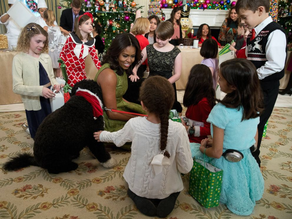 PHOTO: First lady Michelle Obama with dogs Bo, left, and Sunny, behind at right, are surrounded by children in the State Dining Room of the White House in Washington, Dec. 2, 2015.