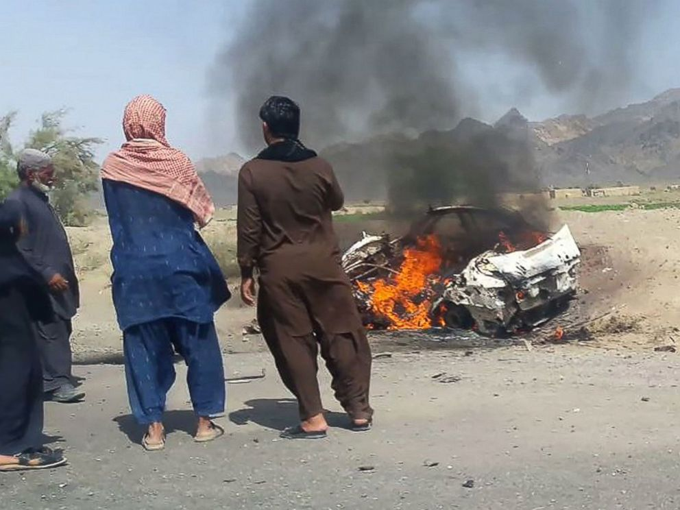 PHOTO: This photograph taken, May 21, 2016, shows Pakistani residents gathering around a destroyed vehicle hit by a drone strike in which Afghan Taliban Chief Mullah Akhtar Mansour was believed to be travelling.