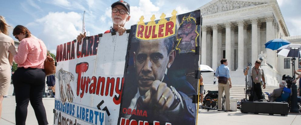 PHOTO: Ronald Brock moves his anti-Obamacare sign as protestors, press, and passersby wait for decisions in the final days of the Supreme Courts term in Washington, D.C. on June 25, 2014.