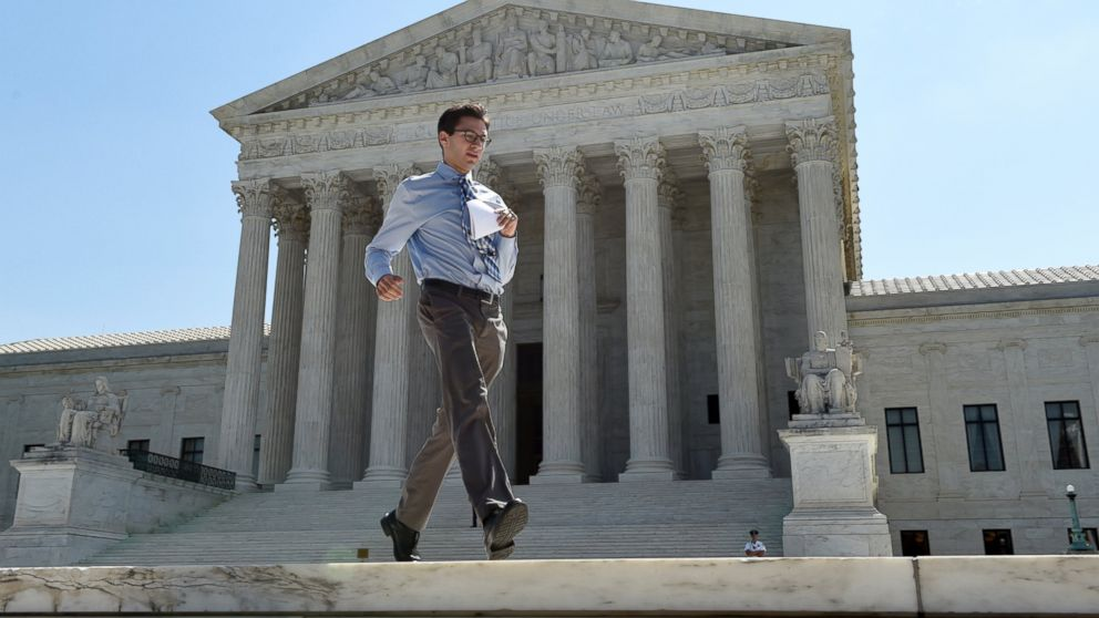 Intern Sam Gringlas runs with one of the Supreme Court rulings in his hand in front of the Supreme Court, June 22, 2015, in Washington.