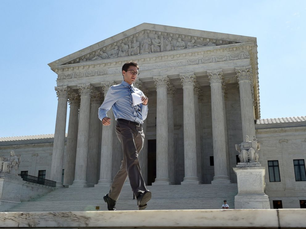 PHOTO:Intern Sam Gringlas runs with one of the Supreme Court rulings in his hand in front of the Supreme Court, June 22, 2015, in Washington.