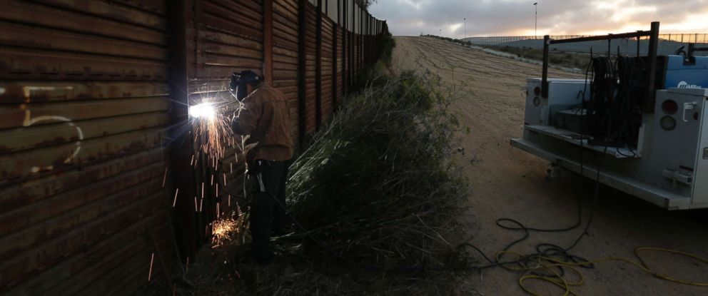 PHOTO: A U.S. Border Patrol agent working with a border wall repair crew welds a section of steel over a hole cut in the border wall in San Diego, Calif., June 13, 2013.