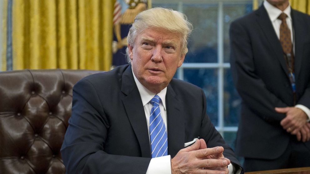 President Donald Trump prepares to sign three Executive Orders in the Oval Office of the White House in Washington, Jan. 23, 2017.