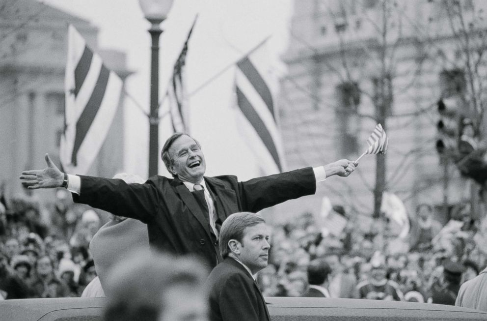 PHOTO: Vice President George Bush waves a small U.S. flag as he and his wife, Barbara, ride in the inaugural parade January 20. He was responding to applause from people lining the parade route, Jan. 20, 1981.