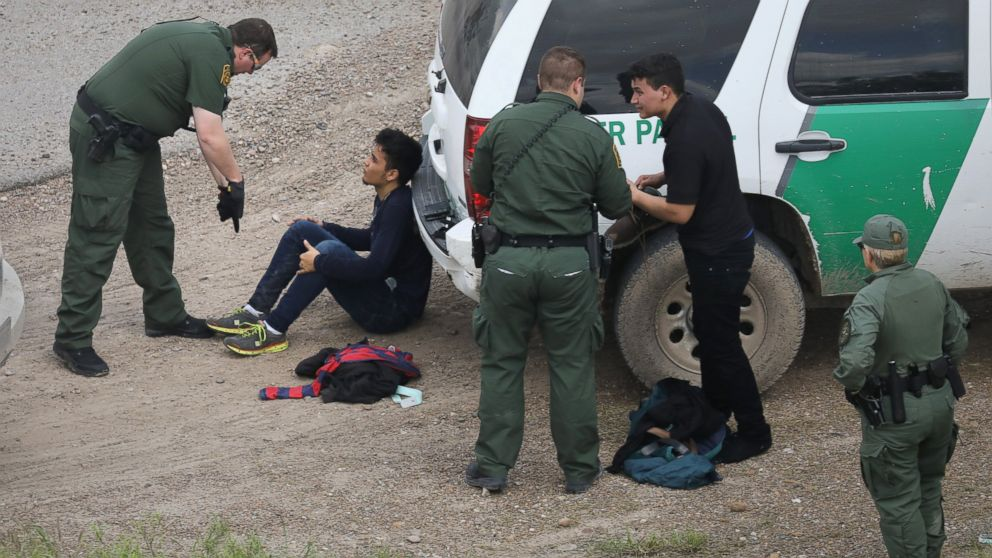 U.S. Border Patrol agents detain two undocumented immigrants after capturing them near the U.S. and Mexico border, on March 15, 2017, near McAllen, Texas.