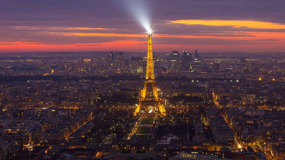 The Eiffel tower shining its spotlight just after sunset, March 16, 2014, in Paris.