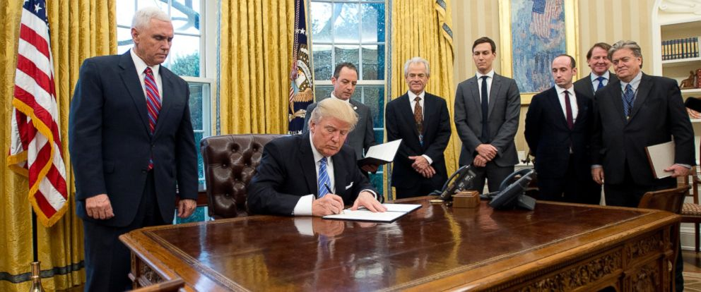 PHOTO: President Donald Trump signs the first of three Executive Orders in the Oval Office of the White House in Washington, DC on Jan. 23, 2017. Steven Miller, Senior Advisor to the President. is third from right.