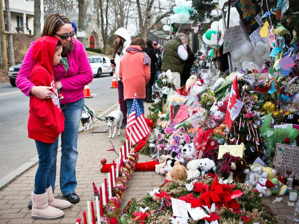 PHOTO: Deborah Gibelli holds her daughter, Alexandra Gibelli, age 9, while looking at a memorial for those killed in the school shooting at Sandy Hook Elementary School, on Dec. 24, 2012 in Newtown, Connecticut.