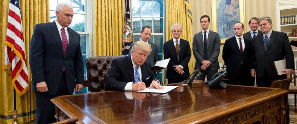 "PHOTO: President Donald Trump signs the first of three Executive Orders in the Oval Office of the White House, January 23, 2017. The ""Mexico City"" executive order, which bans federal funding of abortions overseas, was one of them."