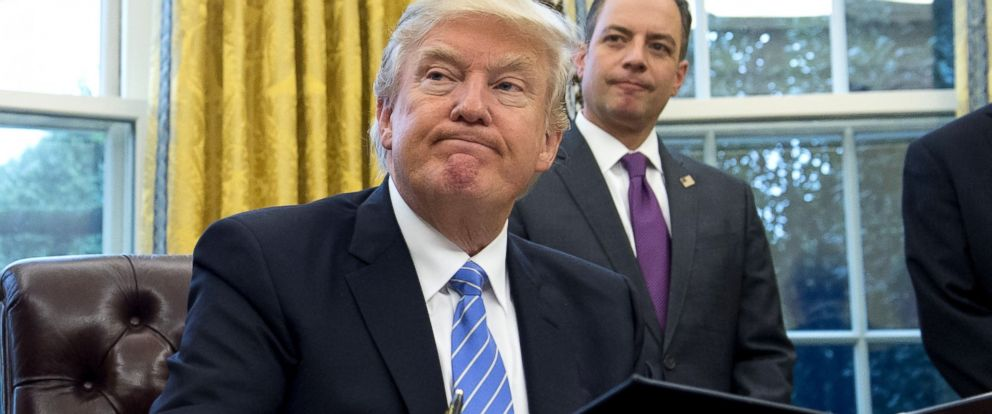 PHOTO: President Donald Trump signs one of three executive orders including withdrawing the US from the Trans-Pacific Partnership trade deal, as Chief of Staff Reince Priebus looks on in the Oval Office of the White House in Washington, DC, Jan. 23, 2017.