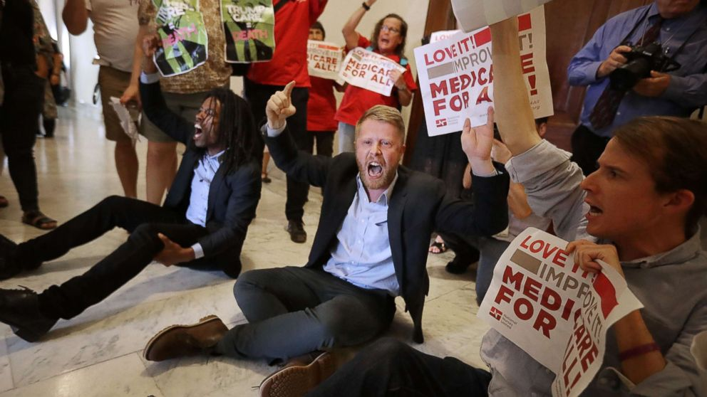 """Demonstrators sit on the ground and chant, """"Kill the bill, kill the bill,"""" outside the offices of Republican Sen. Ted Cruz while protesting against health care reform legislation in the Russell Senate Office Building on Capitol Hill on July 10, 2017, Washington."""