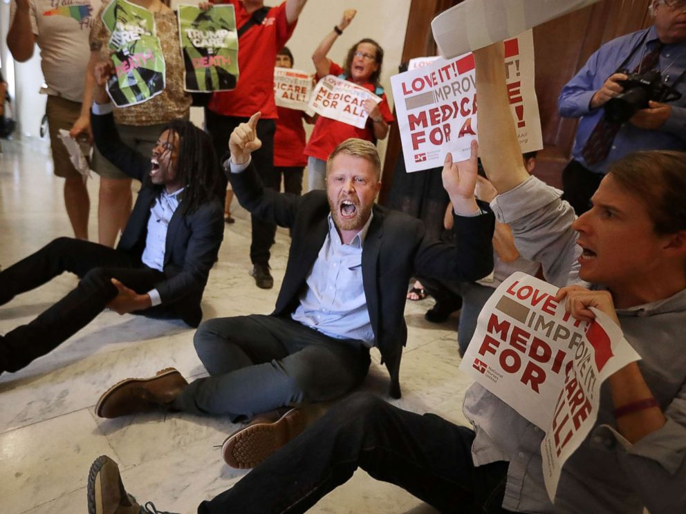 PHOTO: Demonstrators sit on the ground and chant outside the offices of Republican Sen. Ted Cruz while protesting against health care reform legislation in the Russell Senate Office Building on Capitol Hill on July 10, 2017, Washington.