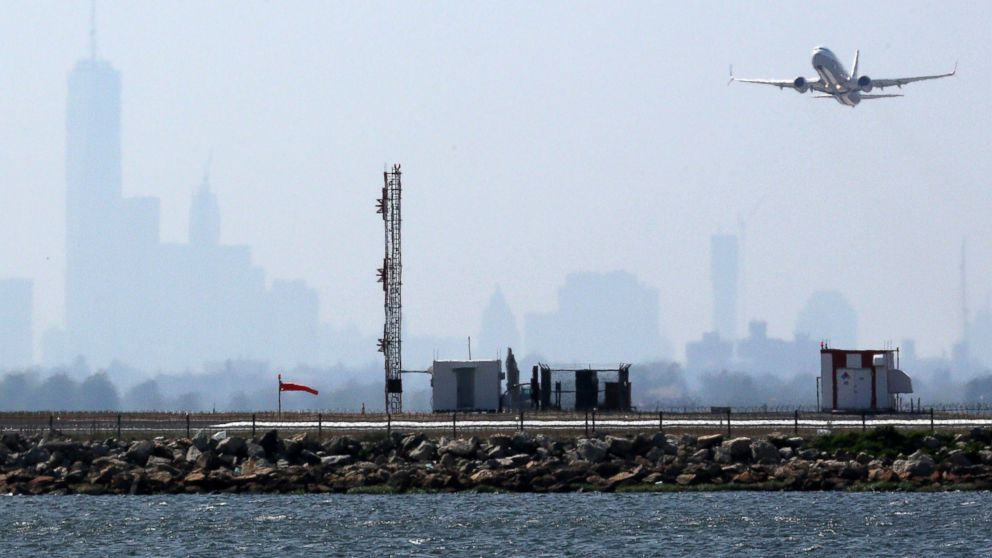 An aircraft takes off from New York's John F. Kennedy Airport against a hazy backdrop of the New York skyline, May 25, 2015.
