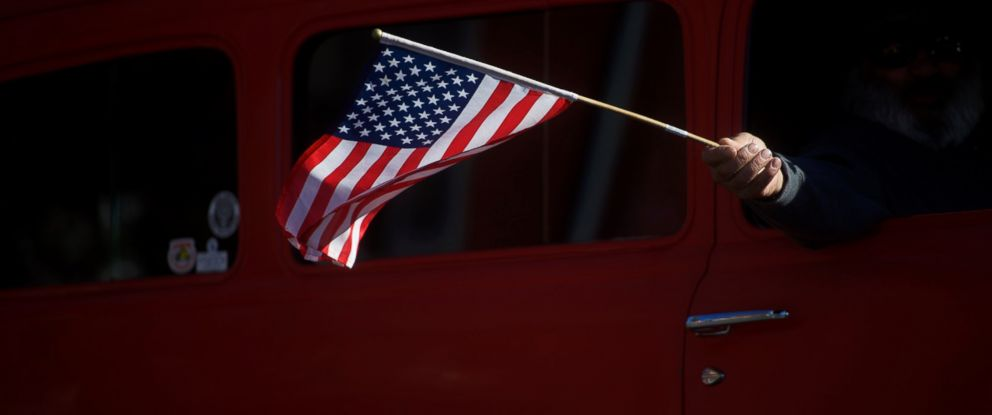 PHOTO: An American flag waves out the window during the Harvest Festival Parade, Oct. 22, 2016 in New Oxford, Pennsylvania.