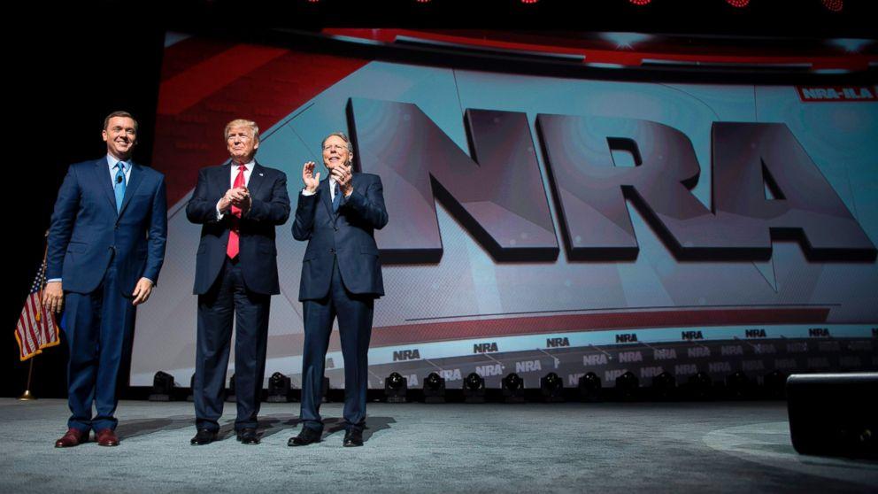 Donald Trump stands with National Rifle Association (NRA) President Wayne LaPierre, right, and NRA-ILA Executive Director Chris Cox during the NRA Leadership Forum in Atlanta, April 28, 2017.