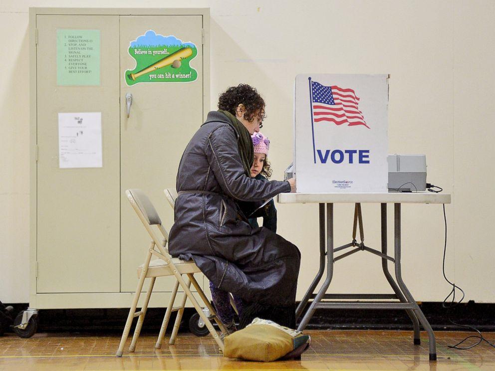 PHOTO: Willa Domina, 6, watches her mother, Emily Katz, vote at a polling station, Nov. 8, 2016, in Durham, North Carolina.