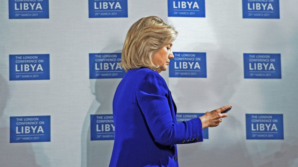 U.S. Secretary of State Hillary Clinton checks her phone at the opening of the Libyan Conference, a meeting of international allies to discuss the next steps for Libya, on March 29, 2011, in London.