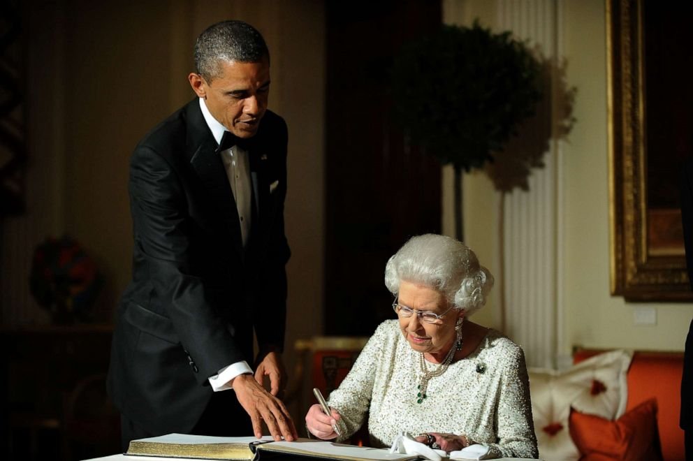 PHOTO: President Barack Obama looks on as Queen Elizabeth signs a guest book after a dinner in London, May 25, 2011.