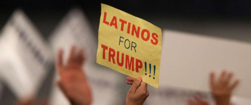 PHOTO: A woman hoods a sign expressing Latino support for Republican presidential candidate Donald Trump at his campaign rally at the Orange County Fair and Event Center, April 28, 2016, in Costa Mesa, California.