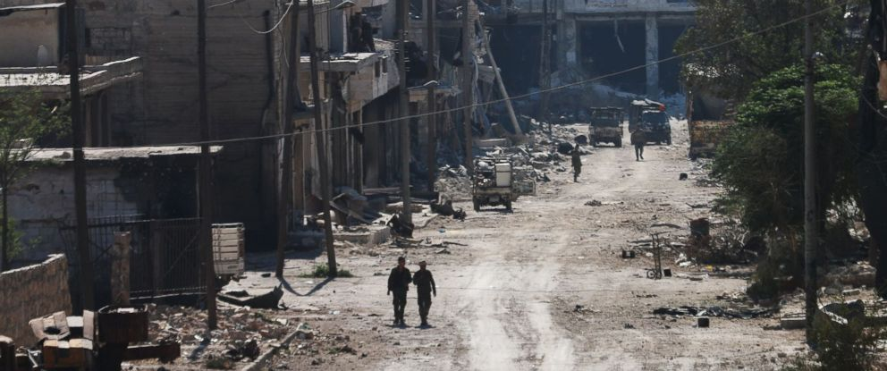 PHOTO: Syrian pro-regime fighters walk in a bombed-out steet in Ramussa on Sept. 9, 2016, after they took control of the strategically important district on the outskirts of the Syrian city of Aleppo yesterday.
