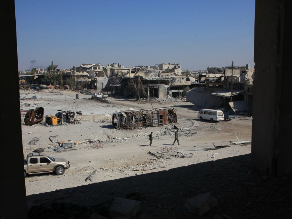 PHOTO: Syrian pro-regime fighters walk in a bombed-out steet in Ramussa on Sept. 9, 2016, after they took control of the strategically important district on the outskirts of the Syrian city of Aleppo the previous day.