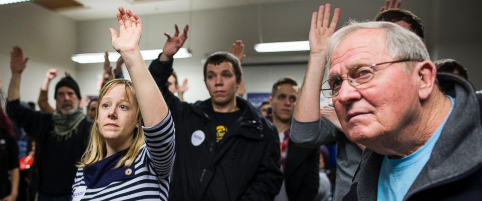 PHOTO: Caucus goers raise their hands to be counted during caucus night at the State Historical Society of Iowa, Feb. 1, 2016 in Des Moines, Iowa.