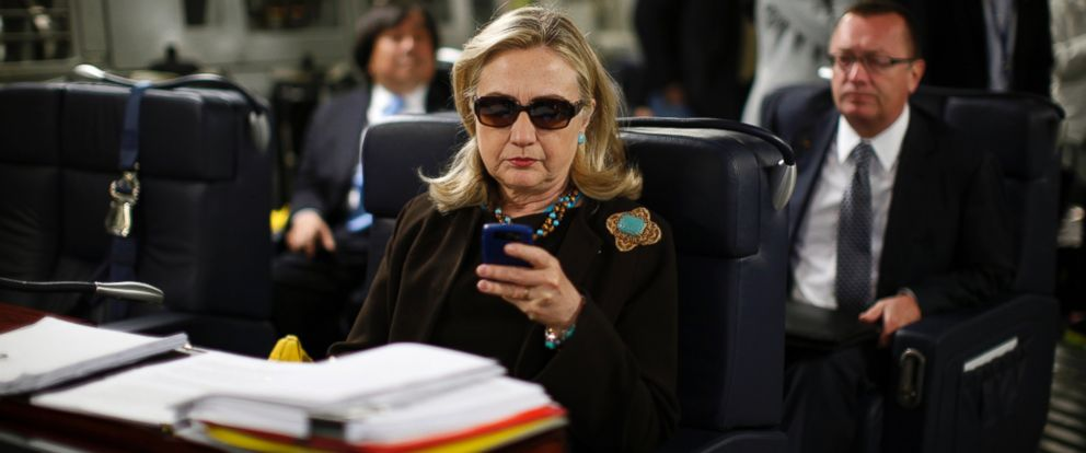PHOTO: Then Secretary of State Hillary Clinton checks her PDA upon departure in a military C-17 plane from Malta bound for Tripoli, Oct. 18, 2011.