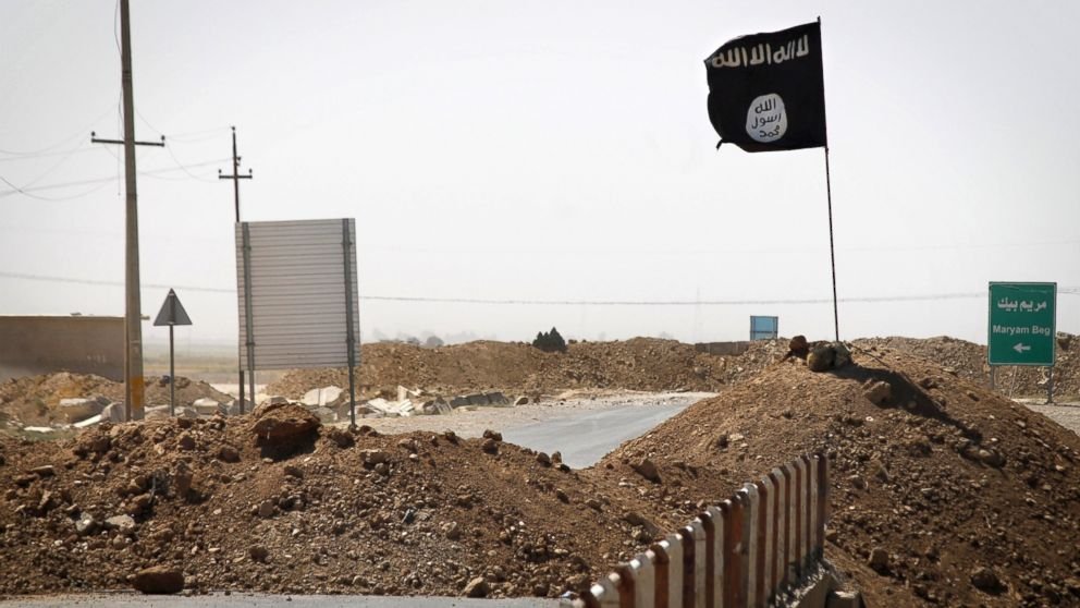 A flag of the Islamic State is seen on the other side of a bridge at the front line of fighting between Kurdish Peshmerga fighters and Islamist militants in Rashad, on the road between Kirkuk and Tikrit, Sept. 11, 2014.