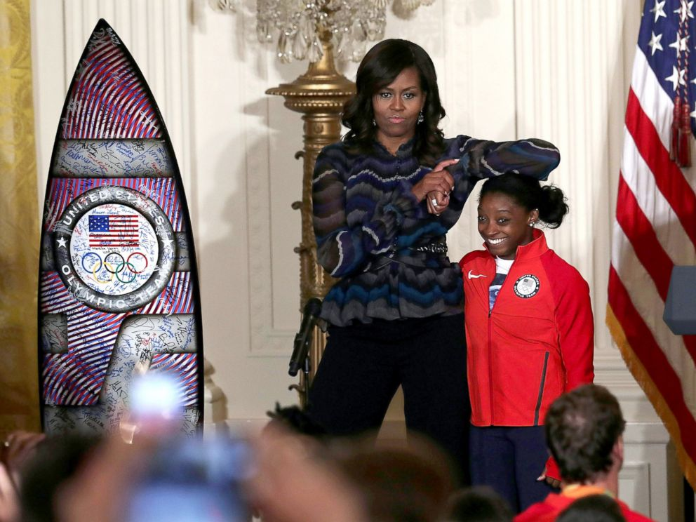 PHOTO: Michelle Obama rests her elbow on the head of Olympian Simone Biles during an East Room event at the White House, Sept. 29, 2016, in Washington.