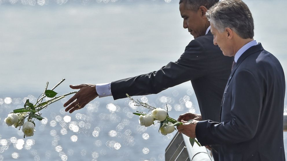 """President Obama and Argentinian President Mauricio Macri throw white flowers into the River as they pay homage to Dirty War's victims at the """"Parque de la Memoria"""" in Buenos Aires,  March 24, on the 40th anniversary of the 1976 military coup."""