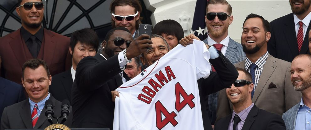 PHOTO: Red Sox Designated Hitter David Ortiz, left, takes a selfie with US President Barack Obama after presenting his a jersey during a ceremony on the South Lawn at the White House in Washington, DC, on April 1, 2014.