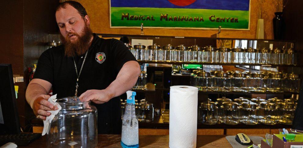 PHOTO: Kurt Britz cleans jars that will hold recreational marijuana at 3D Cannabis Center in Denver, Dec. 30 2013.