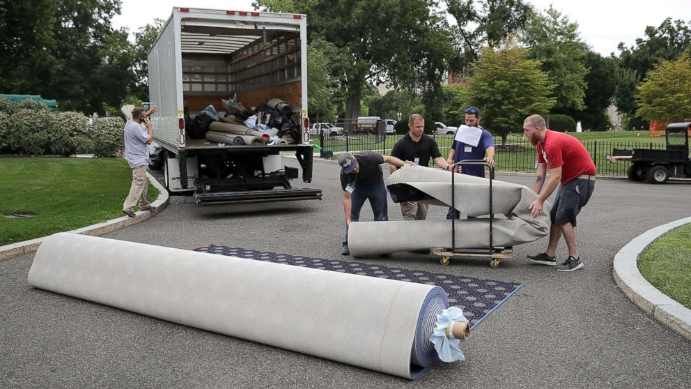 Workers measure and cut new carpeting in the driveway outside the West Wing during renovation work at the White House August 11, 2017 in Washington, DC. The General Services Administration is overseeing the rennovation work during the two week project to update and repair the working area of the White House, including a replacement of the 27-year-old White House heating, ventilation and air conditioning systems.